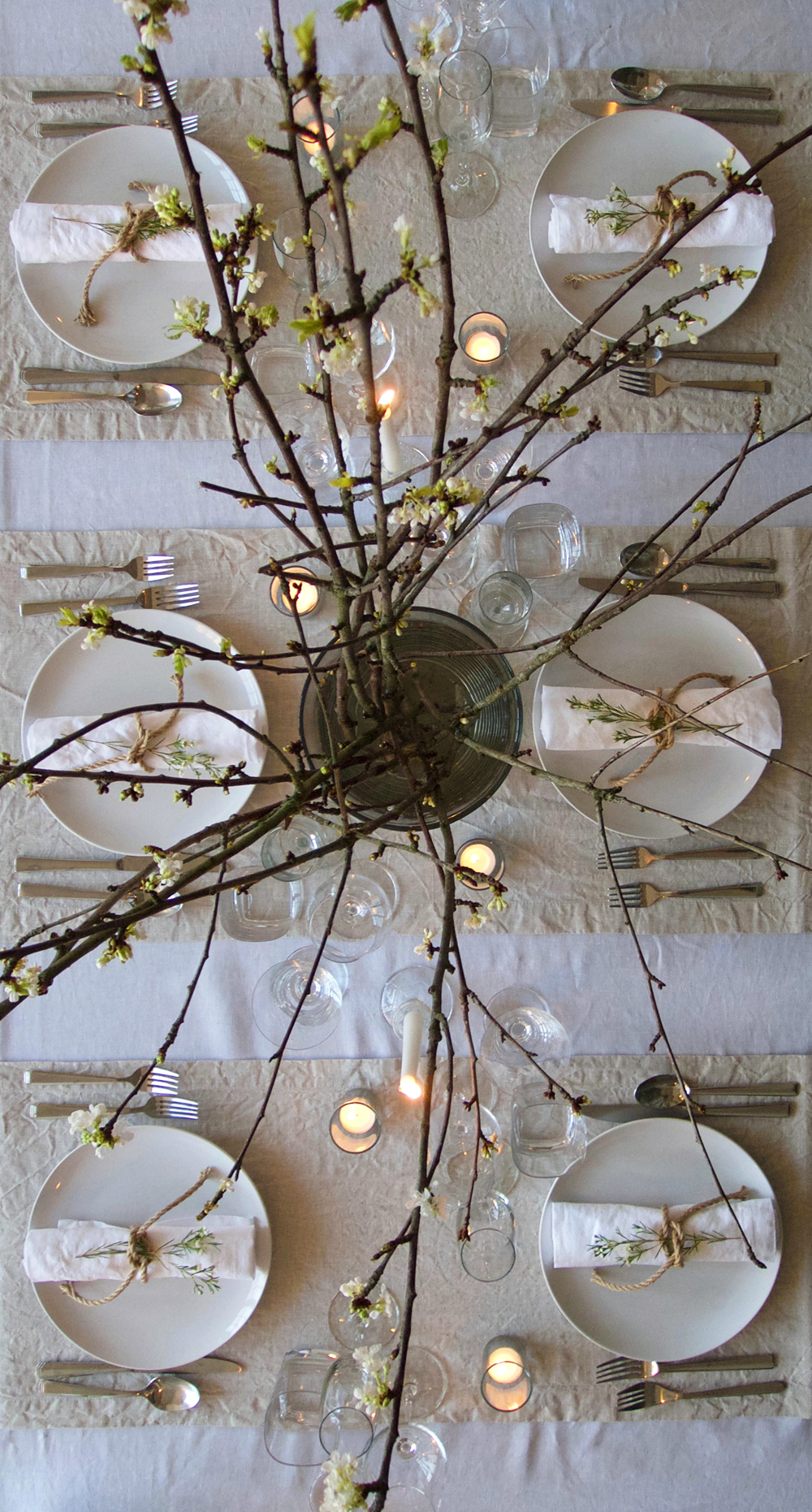 Scandinavian dinner party layering white and natural flax linen table linens, candles and blossom