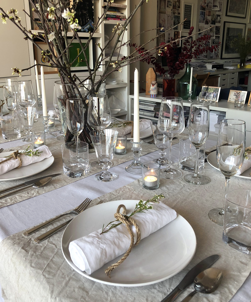 Scandinavian dinner party layering white and natural flax table linens, candles and blossom
