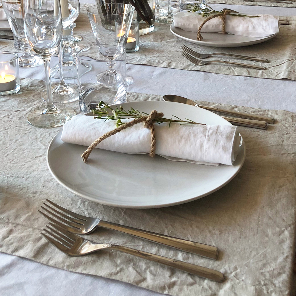 Scandinavian dinner party layering white and natural flax table linens