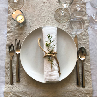 Scandinavian dinner party layering a white linen tablecloth with natural flax linen table runners and white linen napkins