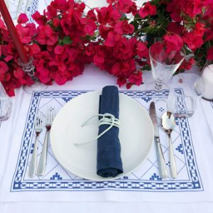 Greek dinner party blue and white linens place setting bougainvillea centerpiece runner
